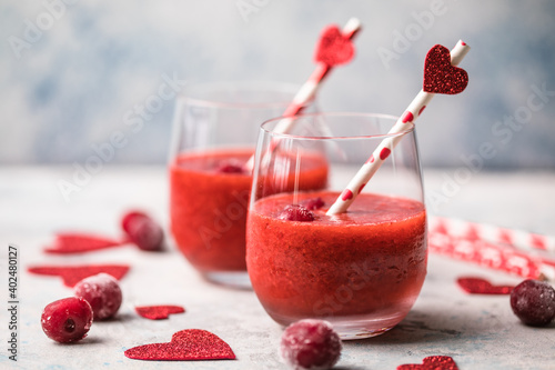 Fresh red cherry  margarita  or daiquiri cocktail with hearts over gray background, valentine day concepts