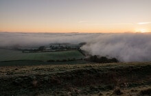 A Dramatic Sunrise View Of Deep Rolling Blanket Ground Level Fog Clouds Over Pewsey Vale, Seen From Martinsell Hill, AONB Wiltshire UK