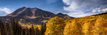 Tree Leaves Changing Color In The Fall In The Rocky Mountains Of Colorado. The Sky Is Blue With A Few Clouds. There Are Lots Of Aspen Trees With Yellow And Orange Leaves.