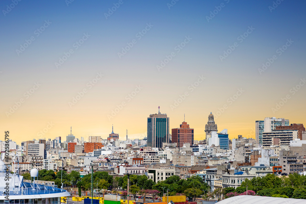 Fototapeta Montevideo, Uruguay-February 28, 2020: View of the city from the port. It is the main commercial port of Uruguay. In the center of the picture, in the distance, you can see the Salvo Palace.