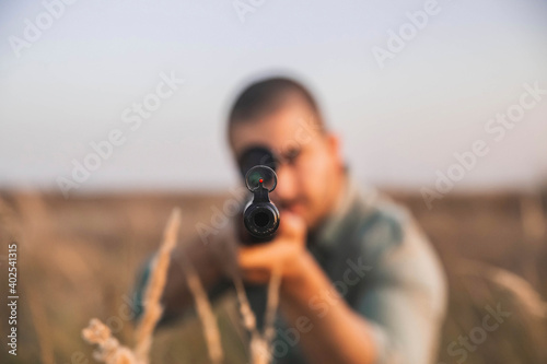 Fotografie, Obraz Hunter aim in the field with a sniper rifle. focus on muzzle