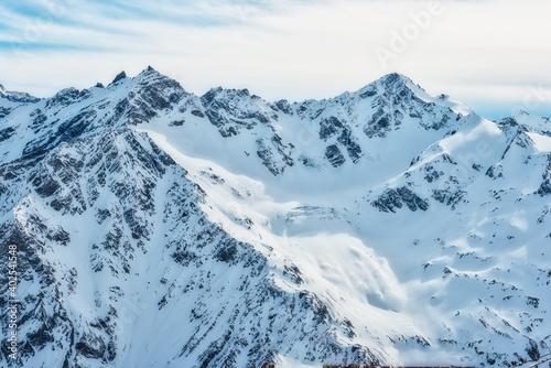 Snowy blue mountains in clouds. Winter ski resort #402541548