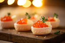 Red Salted Salmon Caviar In Waffle Tartlets On A Wooden Board