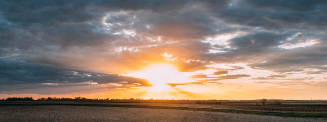 Sun Shine During Sunset Above Empty Spring Countryside Rural Soil Landscape. Field Under Sunny Spring Sky. Agricultural Landscape With Copy Space. Panorama