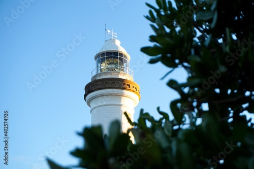 Tela Looking through the leaves at Cape Byron lighthouse at sunset - Byron Bay