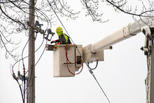 Electrician In Lift Bucket Repairing Power Transformer On A Wooden Pole Outdoors