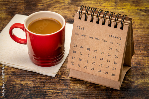 January 2021 - desktop spiral desktop calendar with a cup of coffee, time and business concept