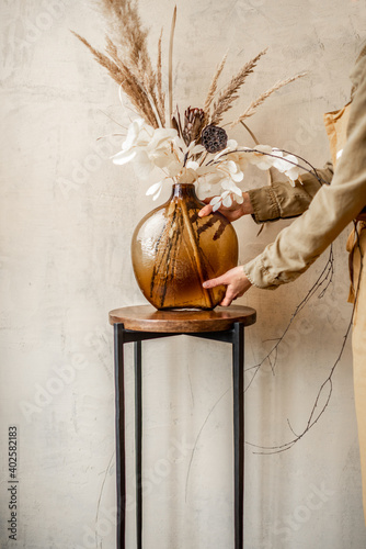 Fototapeta Woman decorating home with a composition of dried flowers and herbs in a glass vase on a beige wall background obraz