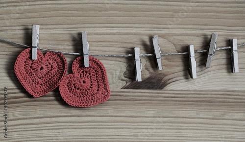 Szydełkowe serduszka na sznurku przypięte drewnianymi spinaczami do bielizny vintage romantic background