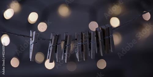 Drewniane spinacze na sznurze w tle światełka vintage background