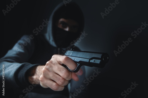 Obraz na plátně man holds a gun in his hands and threatens