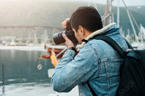 Obraz Male photographer taking pictures outdoors in the port - fototapety do salonu