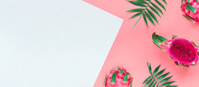 Fresh Organic Pink Dragon Fruit, Pitaya Or Pitahaya With Pink Middle Cut In Half. Pink And White Layered Paper Background With Natural Palm Leaves. Panoramic Image, Banner With Copy-space.