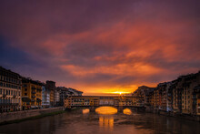 Sun Peeking Through Clouds At Dawn Over The Ponte Vecchio In Florence, Italy