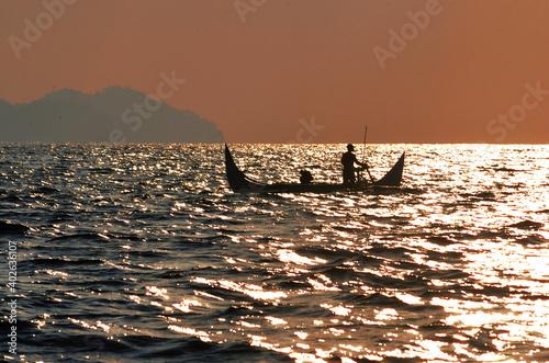 Fototapeta Silhoutte of fisherman in a traditional boat around Kiluan Gulf, Sumatra, Indonesia