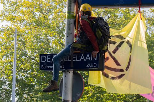 Fototapeta Demonstrator Hanging On A Street Sign During The Rebellion Extinction Demonstrat