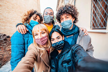 Multiracial Friends Covered By Face Mask Taking Selfie Wearing Winter Clothes - New Normal Friendship Concept With Young Millennial People Having Fun Outside - Bright Filter