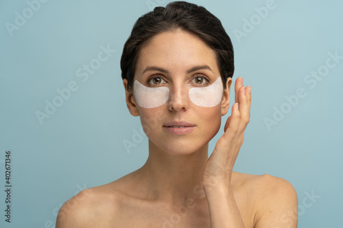 Obraz na plátně Woman applying hydrogel under-eye recovery patches enriched with collagen, vitamin E