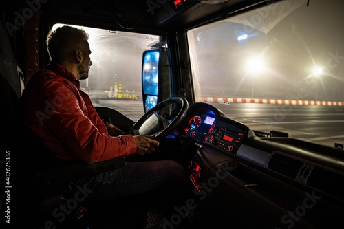 Obraz The driver at the wheel of the truck. Night course. - fototapety do salonu
