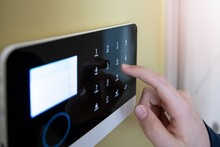 Man's Hand Pressing The Alarm System Button. Home Security.