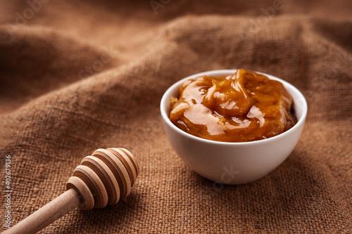 Fototapeta Buckwheat honey in a white bowl near a wooden ribbed honey spoon on a burlap cloth obraz