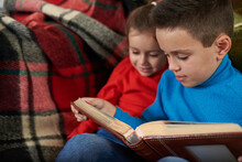 Brother And Sister Watching The Family Photo Album Sitting On The Sofa Against The Background Of A Red Striped Woolen Plaid