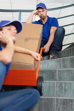 Exasperated Removals Workers Having Difficulty Pulling Trolly Up Stairs