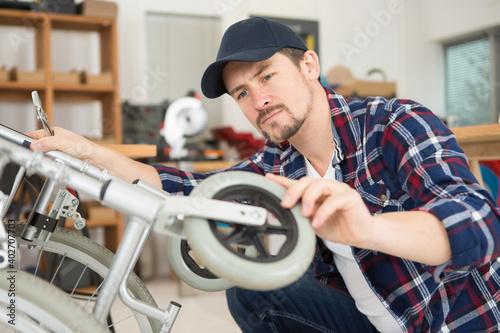 Obraz man repairing a wheelchair in workshop - fototapety do salonu