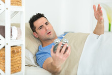 Man In Bed Holding Alarm Clock And Frowning With Disbelief