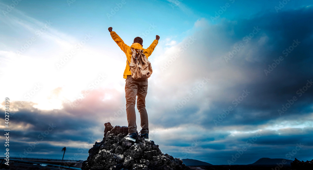 Fototapeta Man with arms up celebrating on top of the mountains - Hiker enjoying freedom on a hill at sunset - Freedom, sport, success and mental health concept