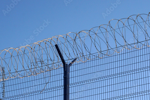 Fotografie, Obraz High fence with barbed wire against a clear and blue sky.