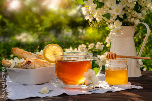 Obraz na plátně Glass cup with tea and lemon, honey dipper, pastries, croissants, white metal jug with a bouquet of jasmine branches on a wooden table among flowering bushes brunch, sunrise, sunset