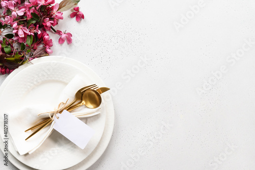 Canvas Print Spring elegance table setting with apple tree flowers, golden cutlery and tag on white table