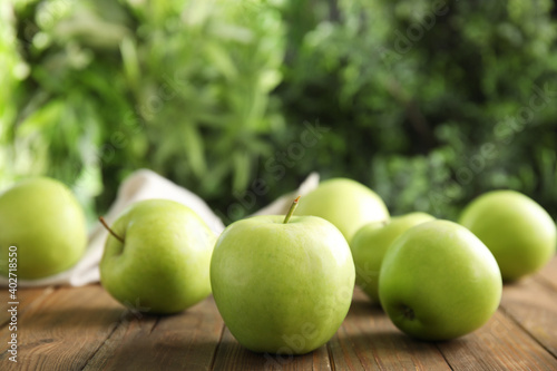 Fotografia Fresh ripe green apples on wooden table against blurred background