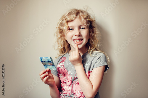 Fototapeta Caucasian blonde girl showing her missing tooth in mouth and holding money from tooth fairy