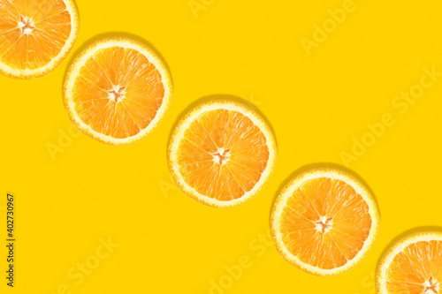 Tableau sur Toile Orange round slices on an orange background diagonally with space for text