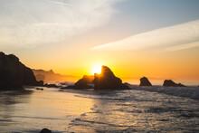 Glowing Orange Sunrise In Malibu. Beautiful Scene With Waves Washing The Sandy Beach.