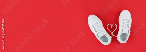 Obraz White sports shoes and heart shape from laces on a red background. Simple flat lay with copy space. - fototapety do salonu