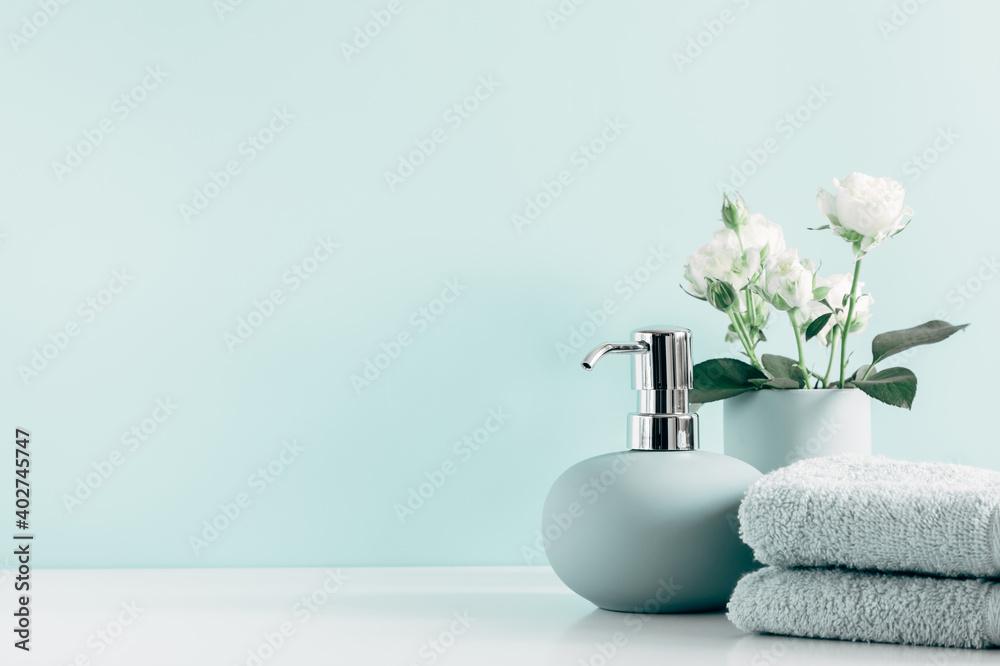 Fototapeta Soft light bathroom decor in mint color, towel, soap dispenser, white roses flowers, accessories on pastel mint background. Elegant decor bathroom interior.