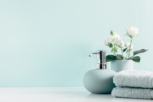 Soft Light Bathroom Decor In Mint Color, Towel, Soap Dispenser, White Roses Flowers, Accessories On Pastel Mint Background. Elegant Decor Bathroom Interior.