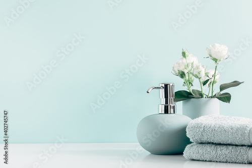 Soft light bathroom decor in mint color, towel, soap dispenser, white roses flowers, accessories on pastel mint background Fototapet