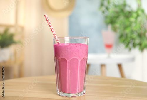 Tasty fresh milk shake on wooden table indoors