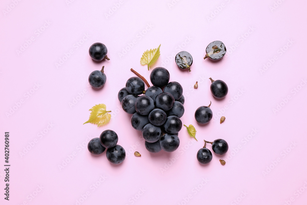 Fototapeta Bunch of ripe dark blue grapes with leaves on pink background, flat lay