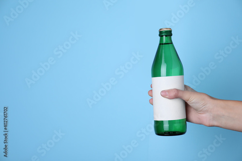 Obraz Woman holding glass bottle with soda water on light blue background, closeup. Space for text - fototapety do salonu