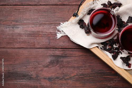 Foto Freshly brewed hibiscus tea on wooden table, flat lay