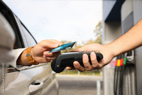 Man sitting in car and paying with credit card at gas station, closeup Fototapet