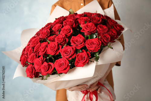 Woman holding luxury bouquet of fresh red roses on light background, closeup