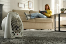 Woman Reading Book In Living Room, Focus On Electric Fan Heater