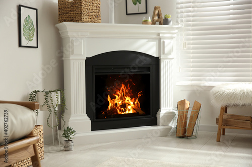 Canvas Print Bright living room interior with artificial fireplace and firewood in basket