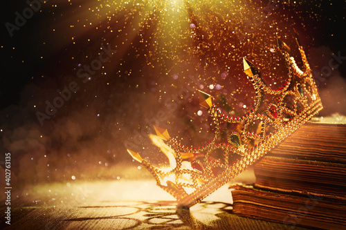 Fantasy world. Beautiful golden crown and old books lit by magic light on table